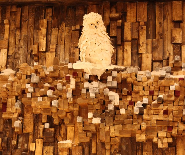 Winter Owl Perched High on a Wall Made of Wood1