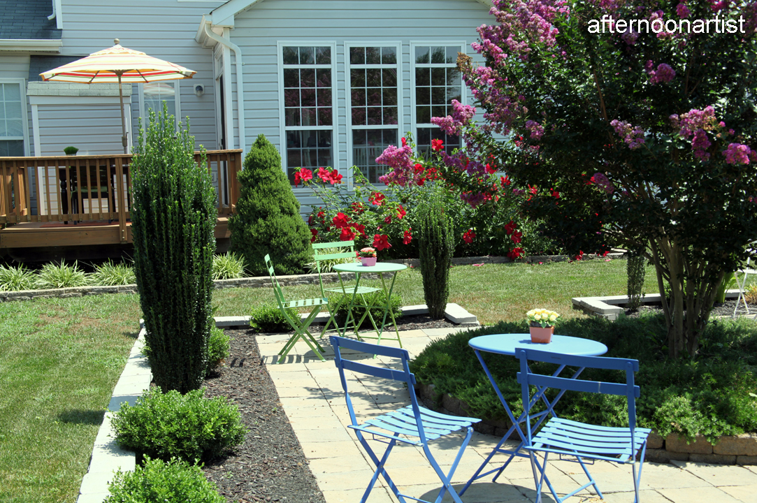 summer garden featuring crepe myrtle, hardy hibiscus, and calla lilies
